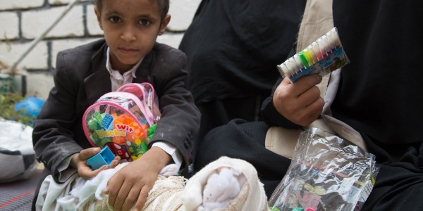 Bambino yemenita con gamba ingessata seduto con giochi in mano