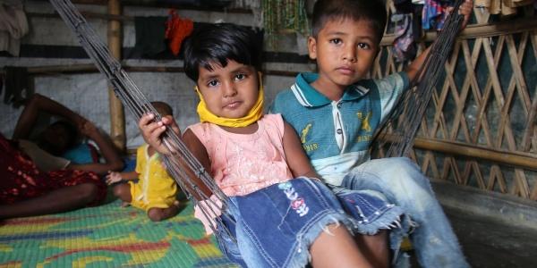 Due bambini Rohingya sono seudti a terra vicini. Il maschio è piu grande e indossa jeans lunghi e una maglietta a maniche corte verde, la bambina ha una canottierina bianca e rossa e una gonna e tiene in mano un peluche giallo