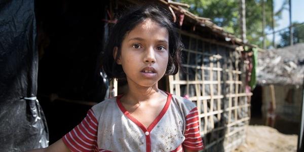 Primo piano di una bambina bengalese mora con capelli corti, la bocca leggermente aperta. Indossa una maglietta grigia con righine rosse.