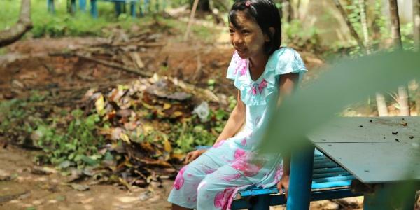 bambina del myanmar con vestito celeste a fiori rosa è seduta su una sedia in mezzo a un terreno circondata da piante