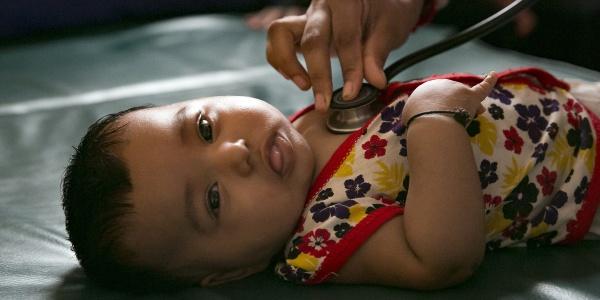 Bambina neonata Rohingya viene visitata stesa con stetoscopio.