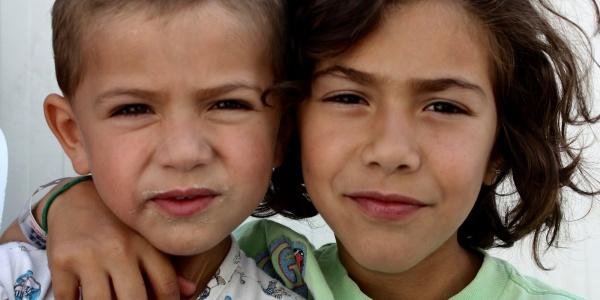due bambini in primo piano, uno con i capelli corti l altro lunghi, uno con il braccio sulla spalla dell altro
