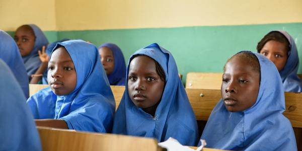 Tre bambine nigeriane della scuola primaria sono sedute a banchi scolastici in legno e guardano davanti a loro. Sono vestite con una divisa celeste e il loro capo è coperto.