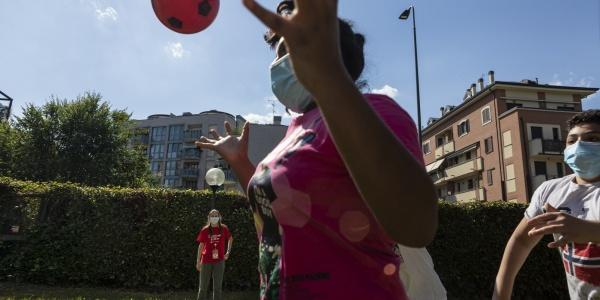 in primo piano una ragazza che gioca con a pallone con altri 2 ragazzi sullo sfondo e una operatrice save the children. Giocano all aperto su un campo verde e indossano la mascherina al volto.