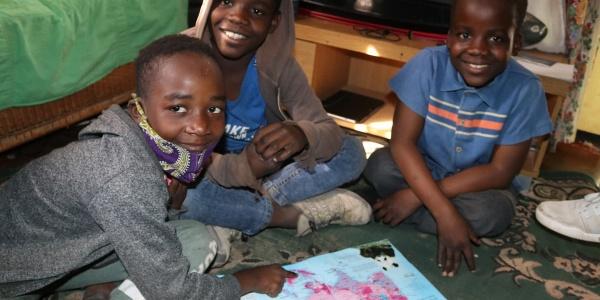 Tre bambini dello Zimbabwe sono seduti a terra intorno a un libro insieme. Hanno gli sguardi sorridenti e guardano in camera