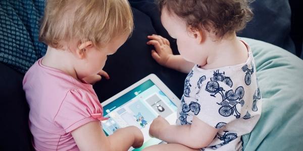 Due bambine molto piccole, una bionda e l altra castana sono sedute di spalle una di fronte all altra e tengono in mano un tablet