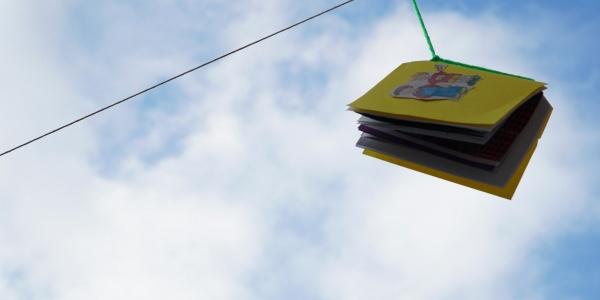 libro colorato appeso a un filo in esterno, sullo sfondo un cielo azzurro con nuvole bianche