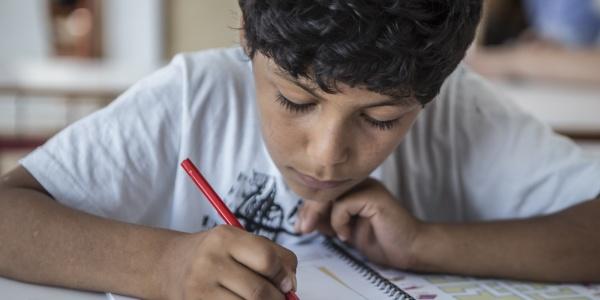 primo piano di un bambino che disegna su un foglio