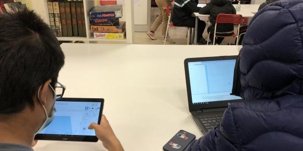 Due bambini di spalle seduti a una scrivania digitano uno su un tablet e uno su un pc.