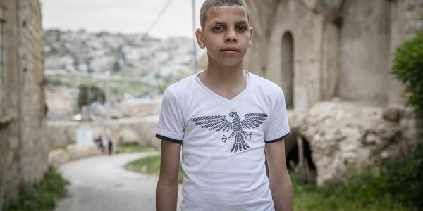 bambino dei territori palestinesi occupati ripreso a mezzo busto con maglietta bianca e sfondo paesaggio sfocato