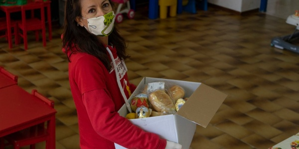 Operatrice save the children con pacco spesa in mano per famiglie vulnerabili durante emergenza coronavirus