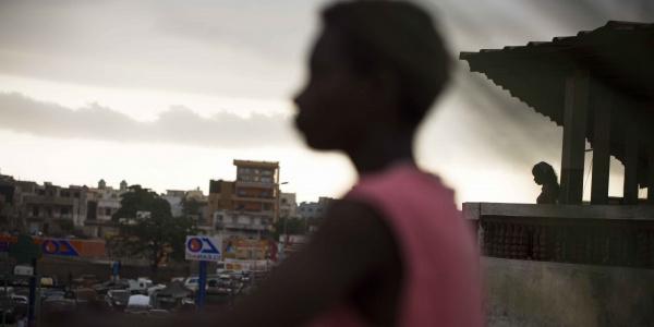 Profilo sfocato di un bambino affacciato dal balcone di un palazzo con la città di sfondo
