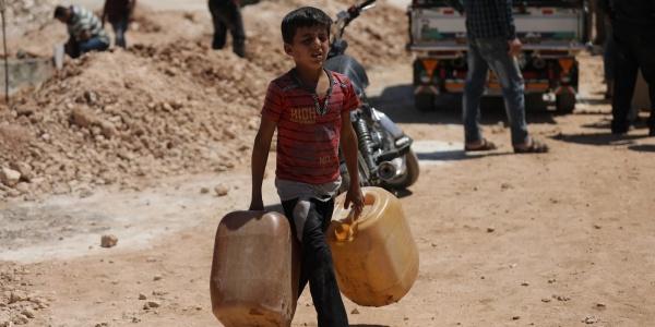 bambino siriano trasporta due taniche di acqua