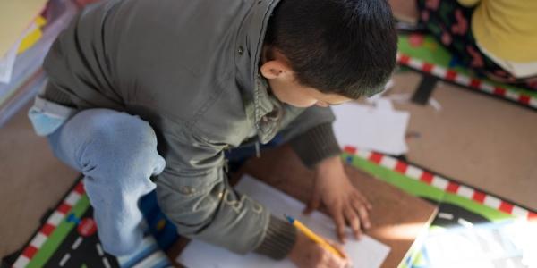 bambino moro di spalle preso dall alto disegna su un foglio a terra