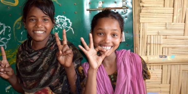 due ragazze sorridenti guardano verso di noi facendo il segno dell ok con le mani