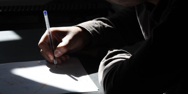 Braccia di un bambino poggiate su un tavolo, una mano scrive con una penna su un foglio bianco. Tutta la foto è in penombra