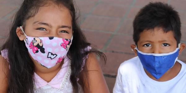 un bimbo e una bambina con mascherine colorate in foto a mezzobusto
