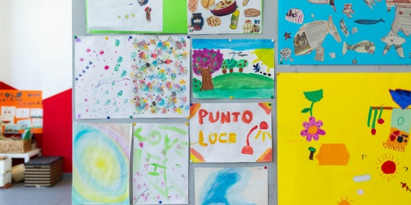 Disegni di bambini attaccati al muro in Punto Luce Save the Children