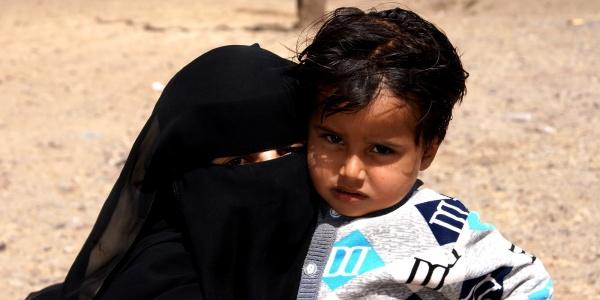 mamma velata con burka tiene in braccio la sua bambina