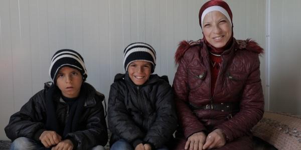 Mamma siriana seduta con i suoi due figli