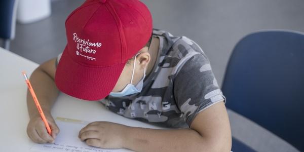 bambino seduto alla scrivania mentre scrive con cappellino rosso in testa e maglietta verde