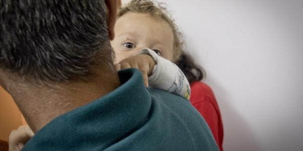 papà di spalle tiene in braccio bambino