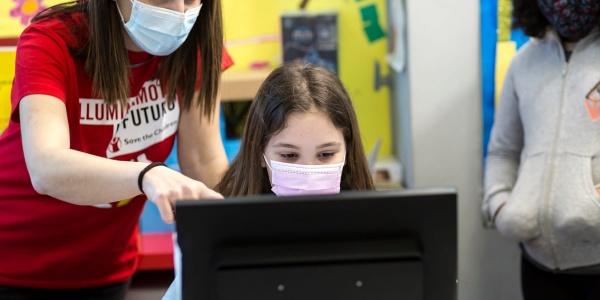 Una bambina davanti al pc e a fianco a lei un operatrice Save the Children accanto a lei indica lo schermo