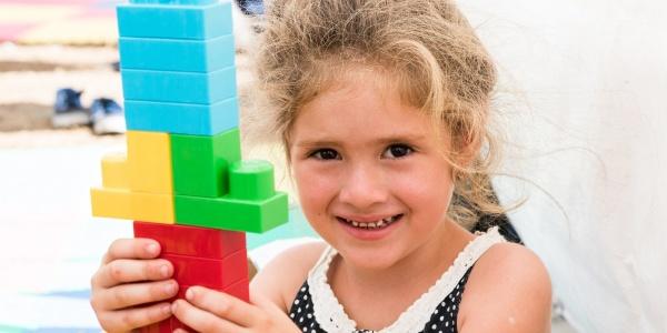 bambina sorridente con in mano una costruzione fatta di Lego colorati