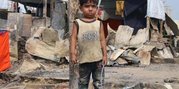 bimbo Rohingya in un campo profughi, vestito con canottiera e pantaloncini sporchi di terra, sullo sfondo un rifugio di lamiere fatiscente