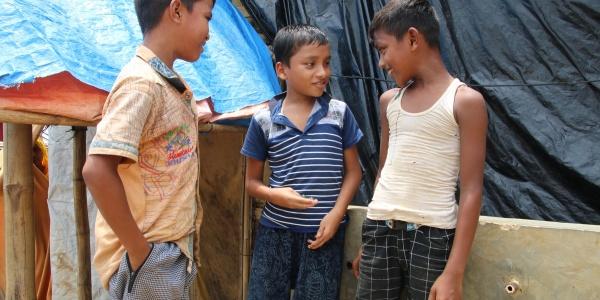 Tre bambini rohingya uno a fianco all altro in piedi parlano tra loro