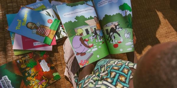 foto dall'alto di bambino che legge dei libricini illustrati colorati