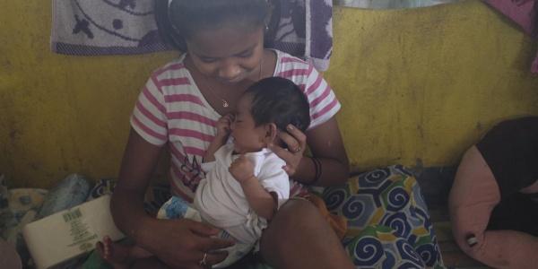 ragazza filippina sfollata tiene in braccio neonato