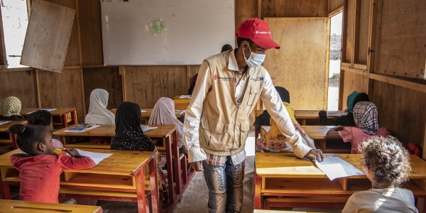 Un operatore save the children in piedi tra i banchi dei bambini in un aula scolastica di un campo rifugiati in Yemen