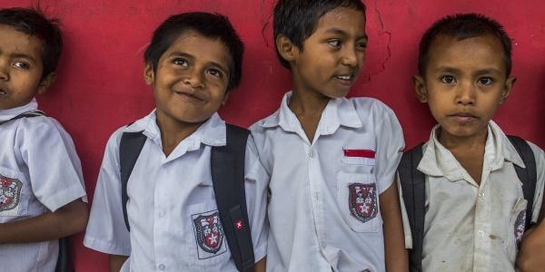 Quattro bambini in divisa scolastica appoggiati al muro