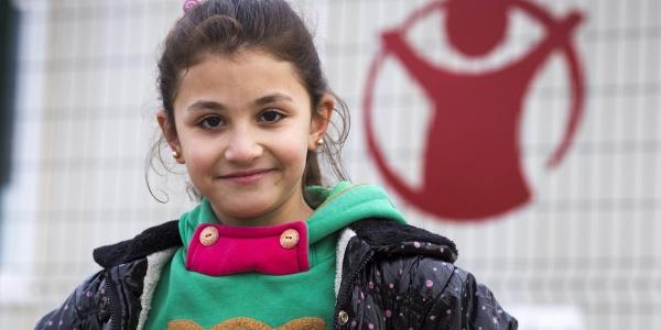 bambina sorridente con maglioncino verde e giacca, sullo sfondo il logo di save the children
