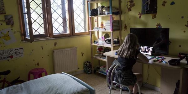 ragazza nella sua camera da letto alla scrivania mentre segue le lezioni in didattica a distanza