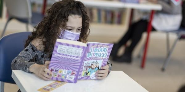 bambina mora con capelli ricci lunghi legge un libro seduta a una scrivania