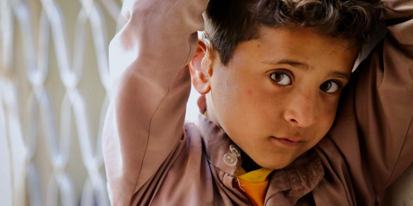 primo piano bambino yemenita che guarda in camera con braccia alzate sopra la testa