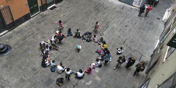 Foto dall'alto di bambini seduti in cerchio in un cortile scolastico