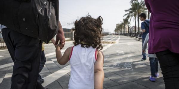 bambina di spalle che cammina mano nella mano con il papà