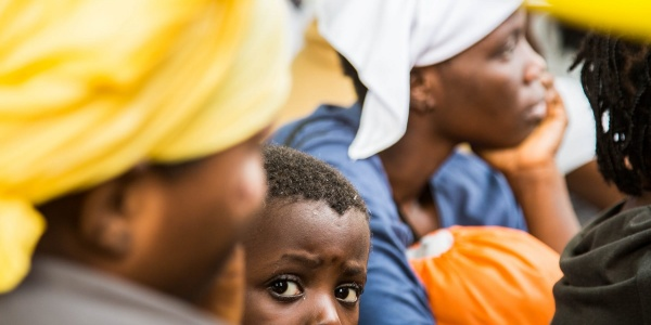 Spunta la testa di un bambino tra i corpi di spalle di alcune donne che sitrovano vicino a lui e che risultano sfocate nell immagine