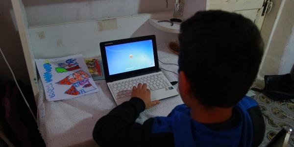 bambino-di-spalle-seduto-davanti-al-computer