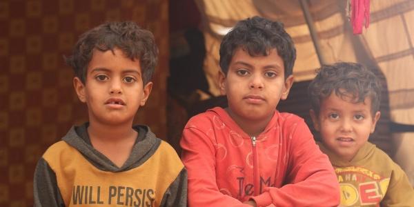 Tre bambini siriani seduti davanti alla tenda del campo in cui vivono guardano in camera. Il taglio è di mezzo busto