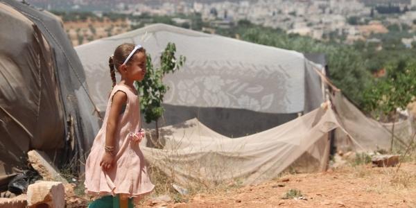 una bambina siriana di profilo cammina in un campo profughi. Dietro di lei si vede una tenda e un paesaggio arido. La bambina indossa un vestito rosa e i pantaloni di una tuta verde.