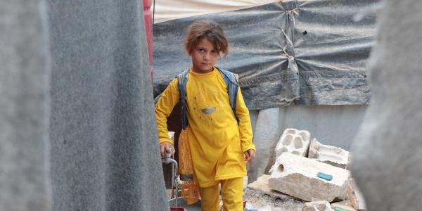 Una bambina vestita di giallo cammina in un campo profughi di cui si vedono alcune parti delle tende e dei rifiuti ingombranti dietro di lei.