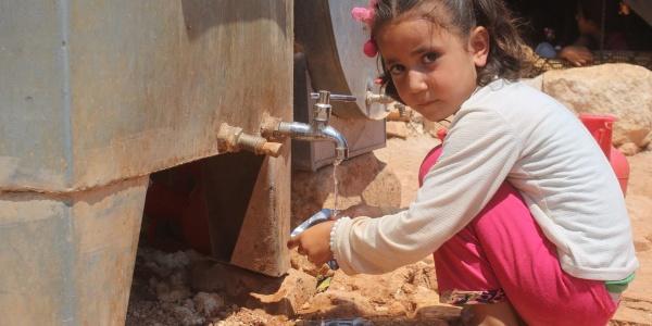 una bambina con pantaloni rosa e maglietta a maniche lunghe bianca è accovacciata di profilo sulle gambe per lavarsi le mani a una fontanella bassa. Ha i capelli biondi legati in codini e guarda alla sua sinistra verso la camera