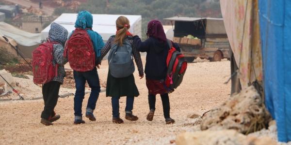 quattro bambini siriani camminano di spalle con gli zaini sulle spalle in un campo per sfollati