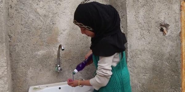 Bambina siriana di profilo vera il sapone sulle mani prima di lavarle al lavandino di fronte a lei.