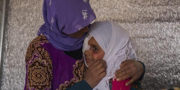 Primo piano di due donne siriane che si abbracciano