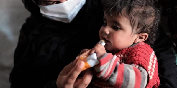 un bambino siriano di circa 3 anni con maglione rosso in braccio a un operatrice vestita di nero con mascherina mangia da una confezione di plumpynut
